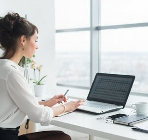 Rear view portrait of a businesswoman sitting on her workplace in the office, typing, looking at pc screen